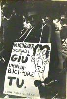 """Manifestazione antinucleare in bicicletta. Un partecipante indossa un cartello con la scritta: """"Berlinguer scendi giù vieni in bici pure tu. Lega anti"""