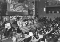 """""""21° congresso straordinario PR. Visione larga della sala. Pannella parla dalla tribuna circondato da manifesti col """"""""sole che ride"""""""", con uditorio. D"""