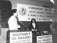 """Rutelli parla dalla tribuna di un congresso del PR del Lazio. Logo e banner. (BN) Attaccato alla tribuna, il cartello: """"Militare? No grazie! Giornata"""