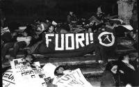 """""""manifestanti sdraiati a Piazza di Spagna (notturno) con uno striscione con su scritto: """"""""FUORI!"""""""" e relativo logo. Altri cartelli contro i missili e"""