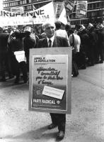 """Marco Pannella, ripreso frontalmente, nel corso di una manifestazione per gli Stati Uniti d'Europa, porta al collo il cartellone: """"Appel a la populati"""