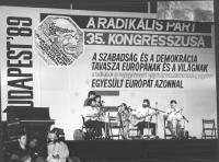 """35° congresso PR. Sul palco concerto con chitarre. Dietro banner con logo PR e scritta: """"a szabadsàg és a demokràcia tavasza euròpànak és a vilàgnak"