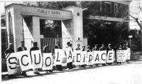 """Manifestazione davanti alla scuola di guerra di Civitavecchia. I manifestanti, ognuno indossando una lettera, compongono la scritta: """"Scuola di pace""""."""