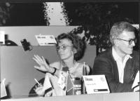 Tribuna di un congresso radicale. Si vede Emma Bonino che compie un gesto come di monito a star calmi. Accanto a lei, Paolo Vigevano. Bianco e nero.