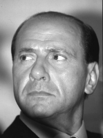 Ritratto di Silvio Berlusconi. Primo piano, sguardo rivolto verso l'alto. Bianco e nero.