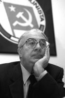 Ritratto di Armando Cossutta. sotto il simbolo del Partito Comunista. Mezzo busto, bianco e nero.