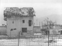 """Una casa devastata. Su uno dei muri, accanto alla porta, è scritto: """"Welcome to Sarajevo"""". Su un'altra piccola costruzione si legge: """"Help Bosnia, now"""