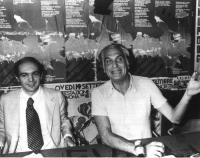 Gianfranco Spadaccia e Marco Pannella seduti al tavolo, durante (presumibilmente) una conferenza stampa. Dietro di loro, manifesti su temi antimilitar