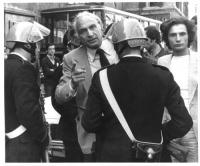 Marco Pannella fra due poliziotti con il casco, armati. Uno dei due ne blocca il passaggio con la canna di un fucile. Bianco e nero. (2 copie + negati