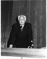 Marco Pannella (che veste un completo nero gessato), parla in piedi, dietro un tavolo, a un microfono. Bianco e nero.