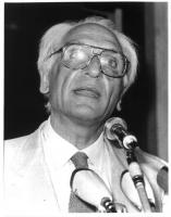 Ritratto di Marco Pannella, che parla al microfono. Mezzobusto, dal basso. Le lenti degli occhiali sono abbagliate dai riflettori dei fotografi. 2 cop
