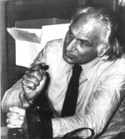 Marco Pannella, in cravatta e maniche di camicia, parla, seduto. Ripreso di tre quarti. Bianco e nero.