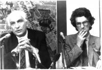 Marco Pannella e Toni Negri seduti accanto dietro un tavolo. Pannella parla al microfono presumibilmente nel corso di una conferenza stampa. Bianco e