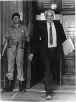 Marco Pannella esce di precipizio da un edificio con un fascicolo in mano. Una sentinella, accanto alla porta, lo osserva. Bianco e nero.