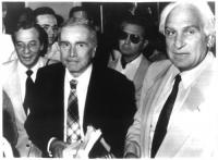 Enzo Tortora e Marco Pannella, in piedi, circondati da altre persone. Bianco e nero.