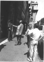 Marco Pannella porge un mazzolino di fiori a una guardia davanti al portone del Partito Socialista, in via del Corso. Pannella reca al collo il cartel