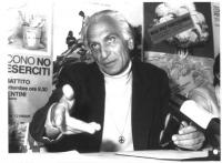 """Marco Pannella (seduto), simbolo della nonviolenza appeso al collo, parla sullo sfondo di manifesti antimilitaristi (vi si legge: """"Mai più Hiroshima"""","""