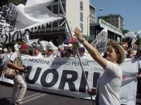 Partecipazione del PR al World Gay Pride. Rita Bernardini innalza la bandiera del PR, davanti allo striscione del FUORI!.