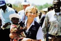 Emma Bonino, commissario UE, in missione in Africa, tiene in braccio un bambino nero.