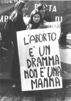 """Manifestazione femminista per la legalizzazione dell'aborto. Una manifestante indossa il cartello: """"L'aborto è un dramma non è una manna""""."""