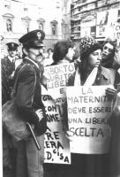 """Manifestazione per la legalizzazione dell'aborto. Cartelli: """"Aborto subito libero e gratuito"""", """"La maternità deve essere una libera scelta""""."""