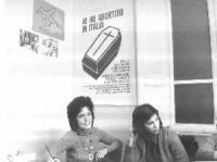 Carla Pietrangeli e Matilde Maciocia (Movimento di Liberazione della Donna) sono sedute di fronte al manifesto che preannuncia una manifestazione a pi