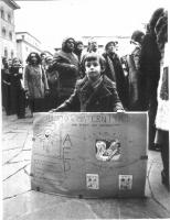 """Nel corso di un corteo, un bambino posa con un cartello intitolato: """"ABORTO E MATERNITA': Due termini non contraddittori""""."""