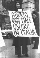 """Una donna indossa il cartello: """"Aborto oggi male oscuro in Italia""""."""