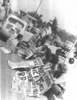 """Marcia antimilitarista. Militanti seduti indossano i cartelli: """"Ci rubano 15 mesi con la naia. Riprendiamoceli con la lotta""""; """"Non c'è democrazia né s"""