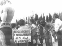 """Marco Pannella, insieme a un gruppo di militanti, a una marcia antimilitarista. Cartello: """"Disobbedienza civile e noncollaborazione armi della rivoluz"""