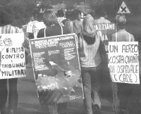 """8a marcia antimilitarista Trieste-Aviano. Una ragazza indossa il cartellone con il manifesto della marcia. Altri cartelli: """"Firma contro i tribunali m"""