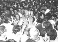 Marco Pannella, circondato da una folla, tiene in mano una cassetta, per la raccolta di contributi.