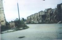 Una strada cecena con case crollate.