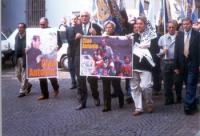 """Funerali di Antonio Russo. Marco Pannella ed Emma Bonino, nel corso del corteo funebre, reggono il manifesto: """"Ciao Antonio""""."""