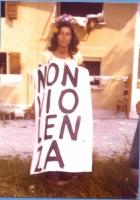 """7a marcia antimilitarista Trieste-Aviano. Liliana Ingargiola indossa il cartello: """"Nonviolenza""""."""