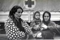 Donne cecene presso un furgone recante il simbolo della croce rossa.