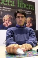 Luca Coscioni, seduto di fronte ai manifesti della campagna elettorale della lista Bonino per le politiche.