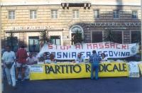 """Tavolo del PR al Pantheon. Dietro, lo striscione: """"Stop ai massacri in Bosnia Erzegovina"""". Primo a sinistra, in piedi: Andrea Tamburi. (La data è pres"""