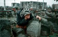Palazzi distrutti e una signora anziana che piange.