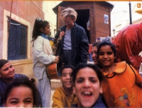 Emma Bonino in un quartiere vecchio della città, circondata di bambini.