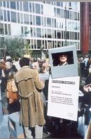 """Manifestazione radicale in occasione del girotondo intorno alla RAI. Un manifestante calza un televisore di cartone, e indossa il cartello: """"RAI dì qu"""