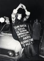 """Notturno. Montecitorio. donna durante una manifestazione alza le mani facendo il segno della vagina. Al collo cartello che dice: """"""""Con questa legge le"""