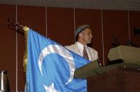 Enver Can, presidente del Congresso Nazionale dell'East Turkestan, alla tribuna del 38° Congresso del PR, mostra la bandiera nazionale.