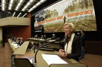 """Emma Bonino, alla tribuna del 38° Congresso del PR. Scorcio del tavolo di presidenza, e vista del banner: """"Globalise freedom and democracy""""."""