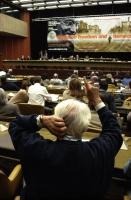 38° Congresso del PR. Vista della platea, della presidenza e del banner, con in primo piano di spalle Pannella, seduto in platea, mentre alza la mano.
