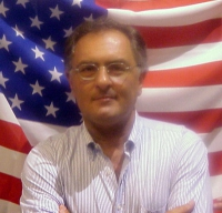 Antonello Marzano (membro della Direzione dei Radicali Italiani), sullo sfondo di una bandiera americana.