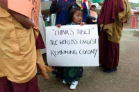 "Una bambina tibetana regge il cartello: ""China's Tibet the world's largest remaining colony"". Foto REUTERS"