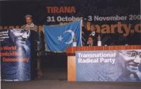 38° Congresso, II sessione. Enver Can, in piedi dietro il tavolo di presidenza, solleva la bandiera dell'East Turkestan. Alla tribuna: un musicista ui
