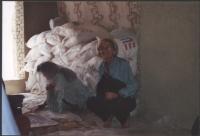 Emma Bonino accovacciata accanto a una donna ricoperta di un velo.