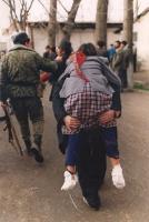 Scena di guerra. Un uomo trasporta sulla propria schiena una donna dai piedi fasciati.